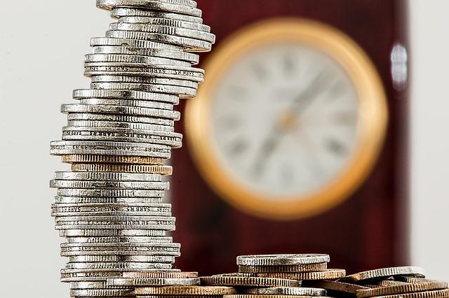 sloupec mincí s hodinami v pozadí