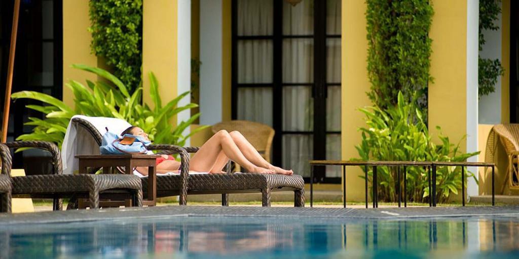 žena na lehátku u bazénu, pohled z vodní hladiny bazénu