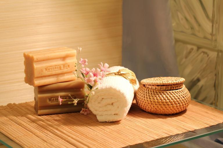 wellness, ručník na stole s květinou, nádobou a mýdlem