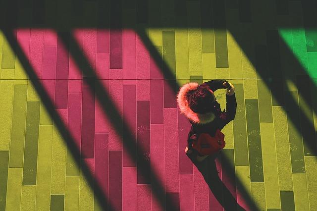 žena fotící s chytrým telefonem na barevném pozadí