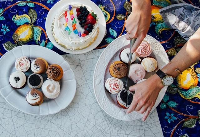 ruce krájí na větším talíři muffin na půl, vedle jsou další talíře s dobrotami